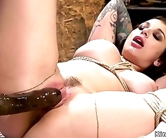 Busty lesbian slave gets strap on in the ass