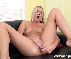 Winsome blonde has fun with dildo on leather couch